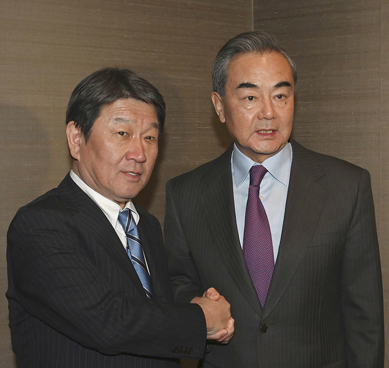 Foreign Minister Toshimitsu Motegi and Chinese State Councilor Wang Yi shakes hands at a security meeting in Munich on Friday. | JAPANESE FOREIGN MINISTRY / VIA KYODO