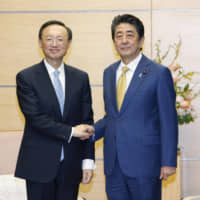 Prime Minister Shinzo Abe greets visiting Chinese foreign policy chief Yang Jiechi on Friday at his office in Tokyo. | KYODO