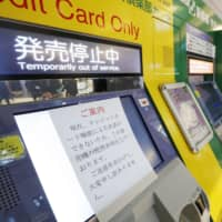 A sign saying credit card payments cannot be made is placed on a ticketing machine at JR Tokyo Station on Monday morning. | KYODO