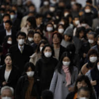 Commuters, many with masks, walk along a sidewalk Tuesday in Tokyo.  | AP