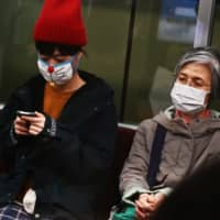People wearing face masks travel on a train in Tokyo on Tuesday. | AFP-JIJI