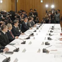 During a meeting held at his office on Sunday evening, Prime Minister Shinzo Abe addresses members of a government task force about devising measures to fight the new coronavirus outbreak. | KYODO