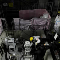 Employees of Tokyo Electric Power Company Holdings Inc. wear protective suits and masks inside a radiation filtering Advanced Liquid Processing Systems (ALPS) at the tsunami-crippled Fukushima No. 1 nuclear power plant in January. | REUTERS