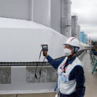A Tepco employee uses a geiger counter next to storage tanks for radioactive water. | REUTERS