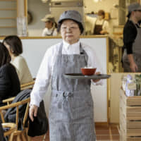 An elderly resident at assisted living facility Ginmokusei Funabashi Natsumi serves customers at a public restaurant on its ground floor in Funabashi, Chiba Prefecture. | KYODO
