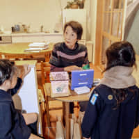 A resident of Ginmokusei Funabashi Natsumi, an assisted living facility in Funabashi, Chiba Prefecture, chats with children who have dropped by to buy snacks at a store inside. | KYODO