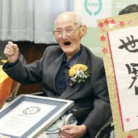 Chitetsu Watanabe, 112, celebrates after receiving a certificate stating he is the world's oldest living man from the Guinness World Records on Wednesday in Joetsu, Niigata Prefecture. | POOL / VIA KYODO