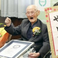 Chitetsu Watanabe poses with his own calligraphy that reads 'world No. 1' in Joetsu, Niigata Prefecture, on Feb. 12, when he received a certificate identifying him as the world's oldest man at age 112. | POOL / VIA KYODO