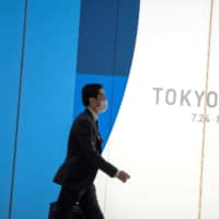 A man wearing a protective mask walks past a Tokyo 2020 billboard near Shinjuku Station in Tokyo. With Friday marking exactly 147 days until the opening ceremony for the Olympics on July 24, a scene from the 1988 post-apocalypse anime 'Akira' has become a talking point on social media. | REUTERS