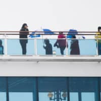 Passengers on the Diamond Princess walk on deck during the cruise ship's two-week quarantine at Yokohama port on Sunday.  | AFP-JIJI