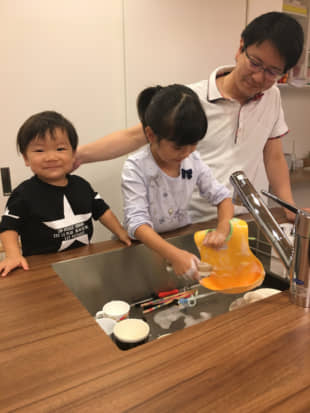 Takashi Omura, an employee of Sekisui House who took paternity leave, watches his children wash the dishes. | COURTESY OF SEKISUI HOUSE / VIA KYODO