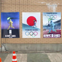 Posters of torch relay runners in protective suits near the Japanese Embassy in Seoul in January | VANK / VIA KYODO
