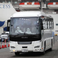A bus carrying passengers from the Diamond Princess on Friday departs from the dock where the cruise ship is under quarantine in Yokohama. | AFP-JIJI