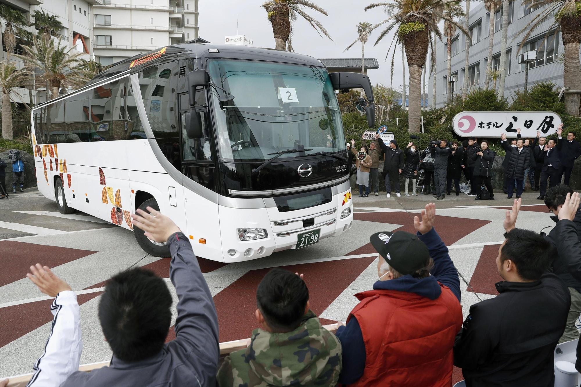 People see off a bus carrying evacuees from Wuhan, the epicenter of the new coronavirus outbreak in China, as it leaves a hotel in Katsuura, Chiba Prefecture, near Tokyo, on Thursday. | KYODO