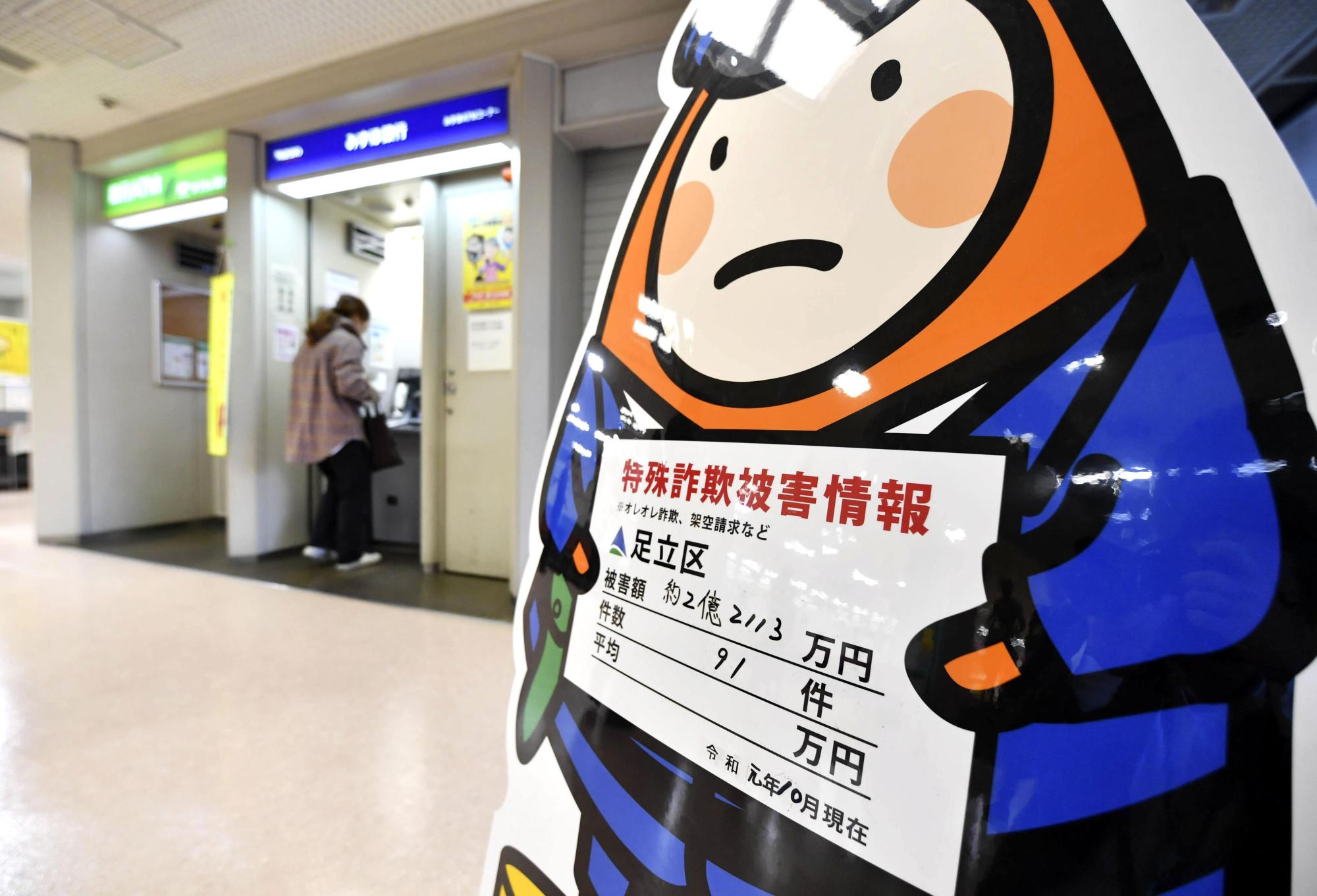 A sign near ATMs at the Adachi Ward Office in Tokyo in late November warns about the amount of money swindlers have taken in special fraud cases. | KYODO