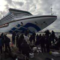 Journalists gather near the Diamond Princess luxury cruise ship as it docks in Yokohama port on Thursday. Ten more people on the ship have tested positive for the coronavirus, raising the number of infections detected aboard to 20. | AFP-JIJI