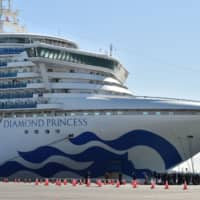 Members of the media gather as the Diamond Princess cruise ship docks at the Daikoku Pier Cruise Terminal in Yokohama on Thursday with around 3,700 people quarantined on board. | AFP-JIJI