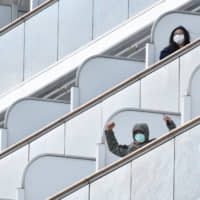 Passengers aboard the Diamond Princess cruise ship step outside upon arriving at the port of Yokohama on Thursday.  | AFP-JIJI
