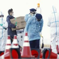 Officials carry supplies for the Diamond Princess cruise liner docked at Yokohama port on Thursday. Forty-one more people on the quarantined ship have tested positive for the new coronavirus, it was announced Friday. | KYODO