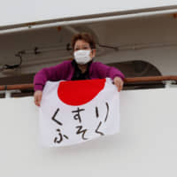 A woman unfolds a Japanese flag that reads 'shortage of medicine' on the Diamond Princess cruise ship on Friday. The cruise liner is currently quarantined in the port of Yokohama as a result of the coronavirus. | REUTERS