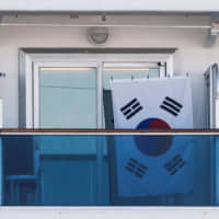 A South Korean flag is seen on the balcony of a cabin on the cruise ship Diamond Princess, as the vessel's passengers continue to be tested for coronavirus, at Daikoku Pier Cruise Terminal in Yokohama, on Thursday. | REUTERS