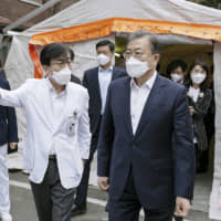Wearing a face mask, South Korean President Moon Jae-in visits a hospital in Seoul last week where people infected with the coronavirus are hospitalized. | SOUTH KOREAN PRESIDENTIAL OFFICE / VIA KYODO