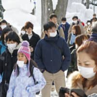 Visitors wear masks at the annual Sapporo Snow Festival in Hokkaido on Tuesday. | KYODO