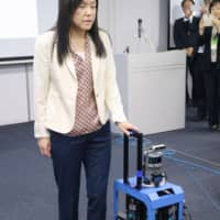 IBM Japan's Chieko Asakawa, a visiting professor at Carnegie Mellon University in the U.S., shows off a suitcase equipped with artificial intelligence technology that is being developed to guide people with impaired vision, in Tokyo's Koto Ward on Thursday. | KYODO