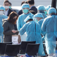 Workers in protective gear assist a passenger after she disembarked from the coronavirus-hit cruise ship Diamond Princess at Daikoku Pier Cruise Terminal in Yokohama on Friday. | REUTERS