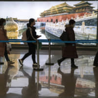 Passengers wearing masks for protection arrive at the airport in Beijing on Feb. 9. China's death toll from the virus has soared to above 1,600 as other nations step up efforts to block the disease. | AP