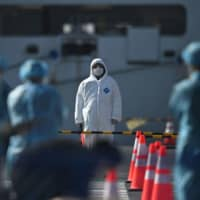 Workers in protective clothes stand before passengers disembarkating from the Diamond Princess cruise ship, in quarantine due to fears over the new COVID-19 coronavirus, at Daikoku Pier Cruise Terminal in Yokohama on Friday. | AFP-JIJI