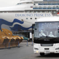 A driver wearing a protective suit is seen inside a bus carrying elderly passengers of the cruise ship Diamond Princess in Yokohama on Friday. | KYODO