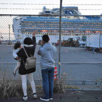 Relatives of passengers wave towards the Diamond Princess cruise ship, with around 3,600 people quarantined onboard due to fears of the new coronavirus. | AFP-JIJI
