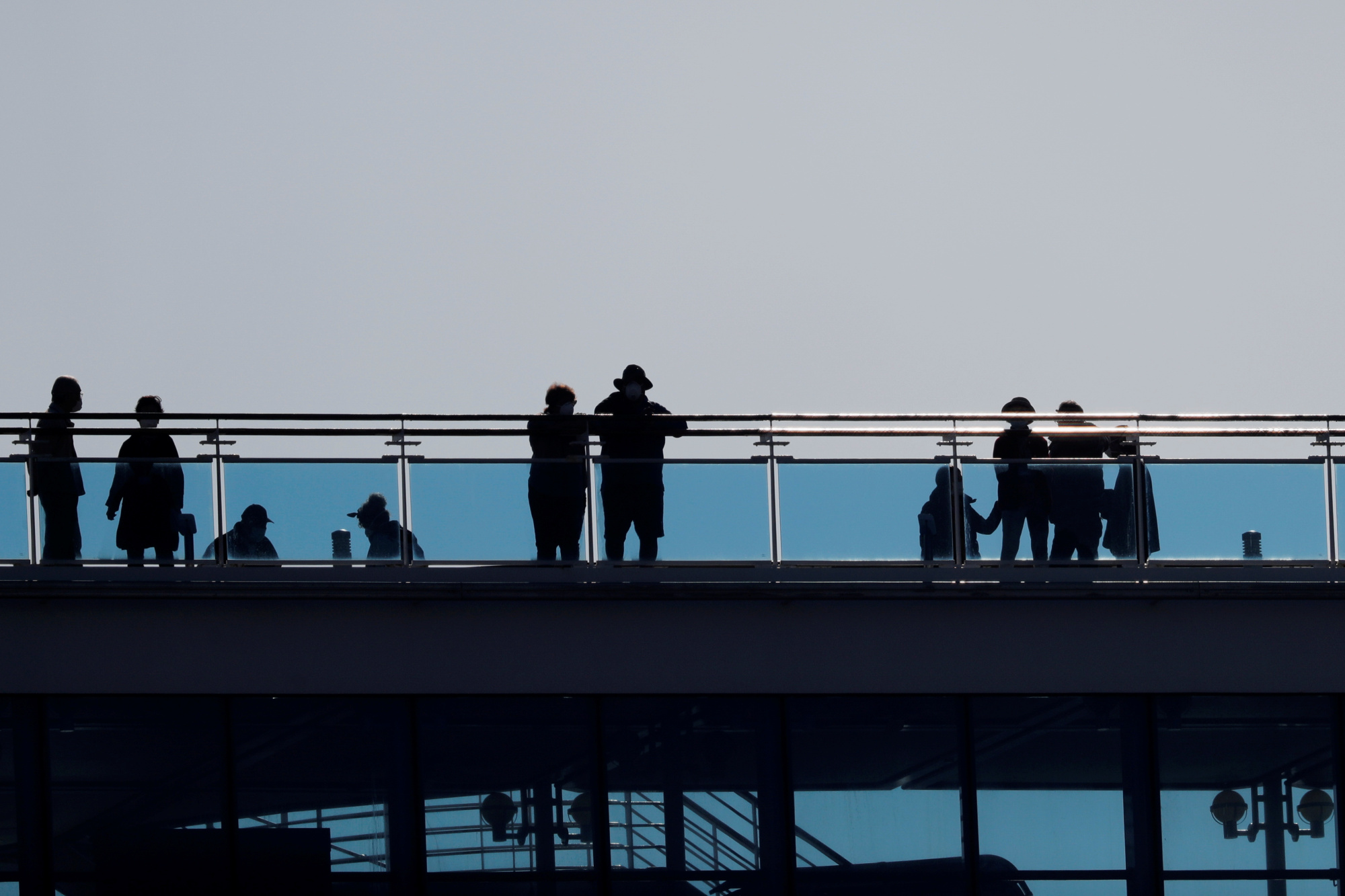 Passengers stand silhouetted on the deck of the Diamond Princess as the cruise ship's passengers continue to be tested for COVID-19 at Daikoku Pier Cruise Terminal in Yokohama on Thursday. | REUTERS
