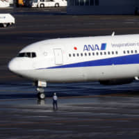 A Boeing 767-300ER plane chartered by the Japanese government and carrying evacuated Japanese nationals living in Wuhan, China, lands at Tokyo's Haneda Airport amid an outbreak of coronavirus on Wednesday. | REUTERS