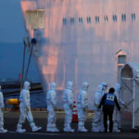 Officers in protective gear enter the cruise ship Diamond Princess on Friday to take a coronavirus patient to the hospital after its arrival in Yokohama. The government plans to announce tourism-support measures against the global outbreak later this week. | REUTERS