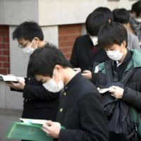 Students wearing masks make final preparations as they head to the University of Tokyo for entrance exams on Tuesday.  | KYODO