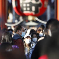 Tourists wear masks in the Asakusa district of Tokyo on Saturday amid the spread of the new coronavirus. | KYODO