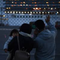 Relatives of passengers watch the Diamond Princess as it sails from Daikoku Pier Cruise Terminal in Yokohama on Tuesday to spend a day at sea dumping wastewater and generating drinking water. | AFP-JIJI