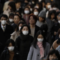 Increasingly, commuters are wearing face masks in Tokyo. On Monday, the government released guidelines for people who fear they have been infected with COVID-19. | AP