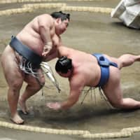 Pushed to the edge: Tokushoryu (left) defeats Shodai on the 14th day of the New Year Grand Sumo Tournament at Ryogoku Kokugikan in Tokyo on Jan. 25. | KYODO