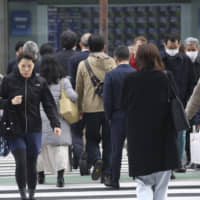 People cross a street in Tokyo on Monday, the day the government announced the economy had contracted at an annual pace of 6.3 percent in the October-December period as typhoons and lower consumer spending took a toll on growth. | AP