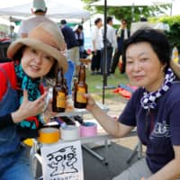 Grains for good: Yoko Higuchi (right) and another volunteer kick back with an official 2019 Soma Tambo Art Project  beer at a summer viewing party. | COURTESY OF THE SOMA TAMBO ART PROJECT