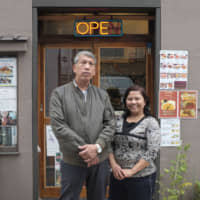 Japan's 'Little Yangon': Than Swe (left) and Than Than Kyaing stand in front of their restaurant, Swe Myanmar, in Tokyo's Takadnobaba neighborhood. | CHISATO TANAKA