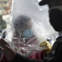 Fear factory: A man wearing a plastic bag over his head enters a supermarket in the central Chinese city of Wuhan, the epidemic's ground zero, on Feb. 10. | AP