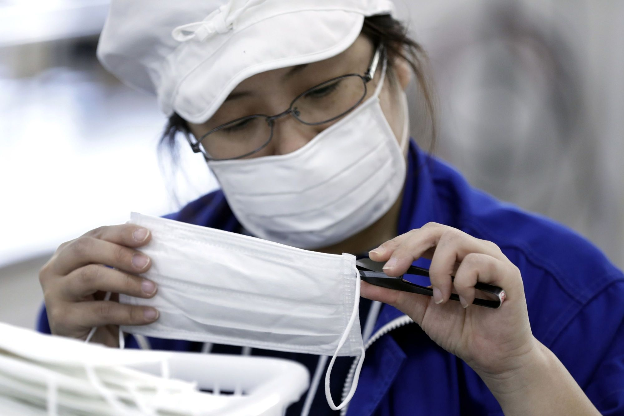 Protective gear: An employee inspects a face mask at a factory in Toyohashi, Aichi Prefecture. Face masks are becoming hard to come by in Japan as fears over CORVID-19 persist. | BLOOMBERG