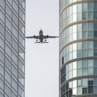 Low blow: A plane flies over central Tokyo on Feb. 3 in a test of new flight paths for passenger aircraft bound for Haneda Airport, as the air hub looks to boost capacity in time for the 2020 Olympics. | KYODO
