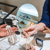A clerk at Jinbo Pearls in Otsu shows a customer jewelry made from Lake Biwa pearls. | PHILIPPE VOISIN