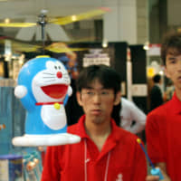 Taiyo Kogyo Co. employees demonstrate a radio-controlled Doraemon helicopter toy. | BLOOMBERG