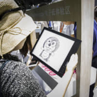 A woman looks at a sketch of the character Doraemon at an exhibition in Shanghai in 2018. | BLOOMBERG
